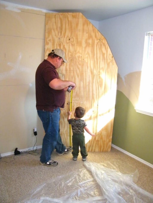 Le papa installe une planche de bois contre le mur, lorsqu'il ...