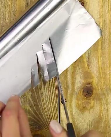 Elle coupe des lanières dans une feuille de papier d'aluminium pour une raison inhabituelle...