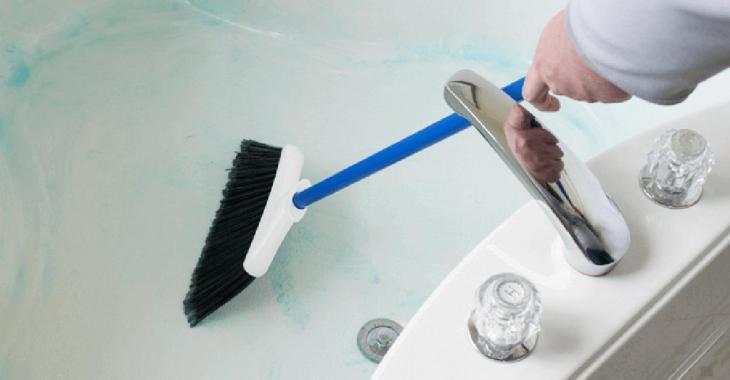 Elle prend un balai et le passe dans son bain afin de nous montrer une façon efficace de le nettoyer