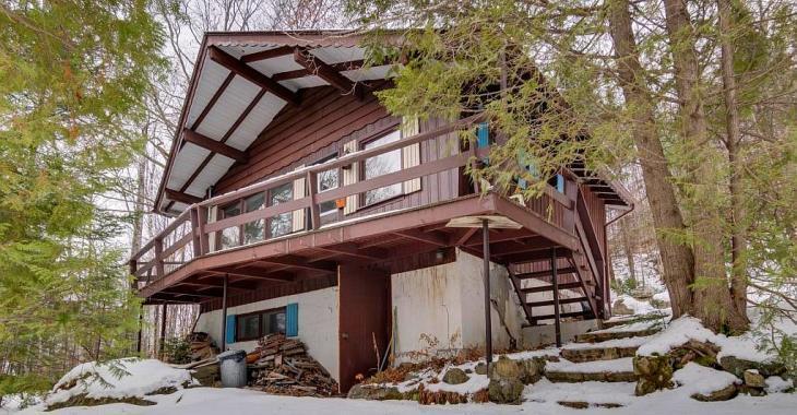 Sise sur un immense terrain, cette maison-chalet à flanc de montagne se vend seulement 73 000$