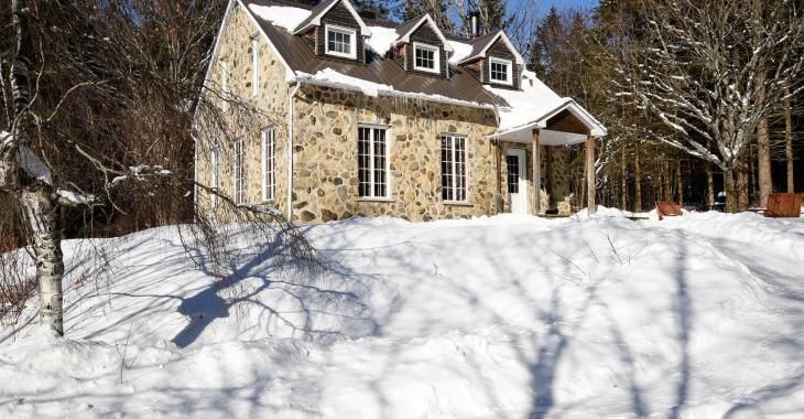 Autrefois une école de rang, ce cottage en pierre remis à neuf offre un bel espace de quiétude tout entouré d'arbres matures