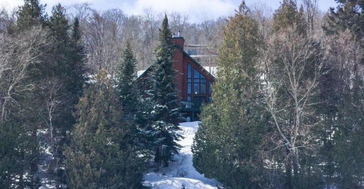 Dans Lanaudière, cette propriété nichée au creux des arbres offre une vue époustouflante sur le lac à partir du balcon