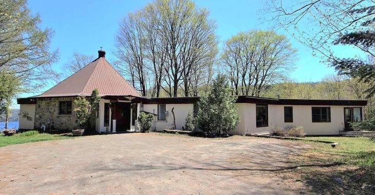 Sis sur un vaste domaine privé surplombant un lac, ce bungalow de 1974 a un style qui surprend dans un tel environnement