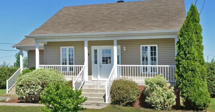 Cette charmante maison de 219 900 $ propose une fenestration abondante, des planchers de bois et une belle cour intime bordée par une haie
