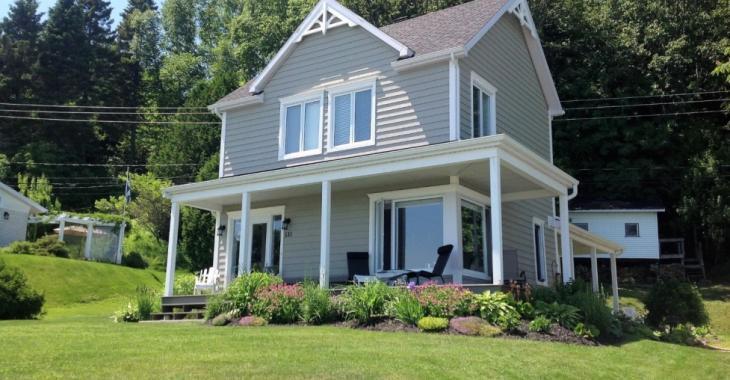 Cette charmante maison vous offre un emplacement de rêve face au fleuve