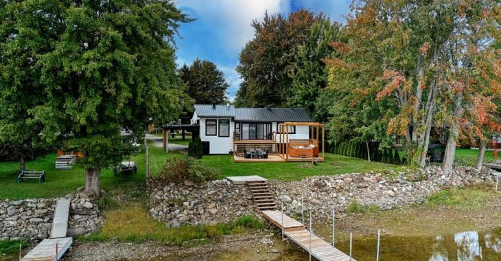 Succombez aux charmes de ce parfait cottage riverain dont l'intérieur a été entièrement métamorphosé avec savoir-faire